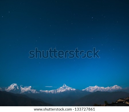 Annapurna range with Fishtail Mountain (Machapuchare Mountain - 6997m) in the middle with other Annapurna Mountains on the left and right from Dhampus Gurung Cottage (1670m or 6680ft from sea level). - stock photo