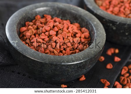 Annatto Seeds - Annatto (achiote) seeds in a black bowl. - stock photo
