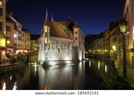 ANNECY, FRANCE - SEPTEMBER 16, 2012:  The ancient fortress-prison on an island in the river. Fortress beautifully lit and is reflected in the smooth water.
