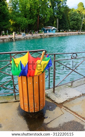 Annecy lake after rain. Broken colorful umbrella in garbage can. Park at background.