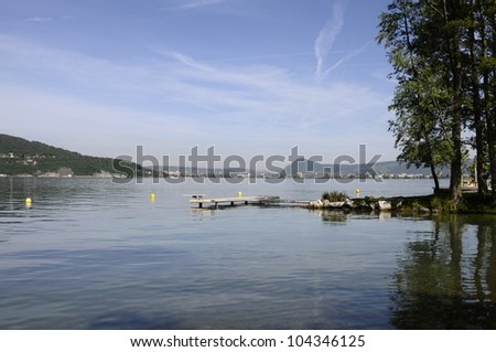 Annecy lake on morning with pontoons and some trees