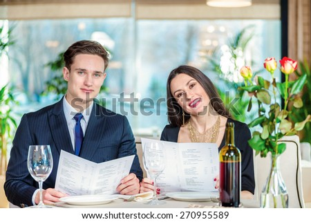 Anniversary and love romantic dinner in a restaurant. Young loving couple while visiting a restaurant menu holds in his hands and with a smile looking at the camera - stock photo