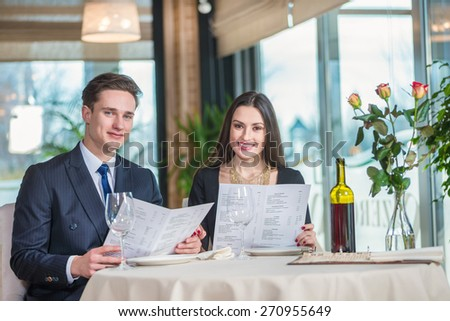 Anniversary Celebration at the restaurant. Romantic dinner in the restaurant. Young loving couple while visiting a restaurant menu holds in his hands and with a smile looking at the camera - stock photo