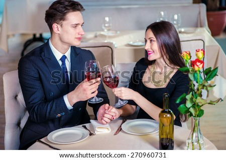 Anniversary celebration. Romantic dinner in the restaurant. Young loving couple visits a restaurant and raised their glasses of wine and looking on  each other - stock photo