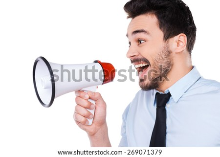 Announcing good news. Side view of happy young man in shirt and tie holding megaphone and shouting while standing against white background - stock photo