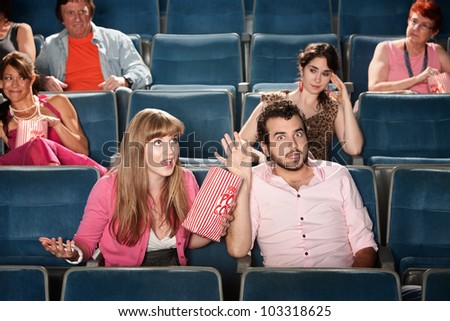 Annoyed audience and arguing couple in movie theater - stock photo
