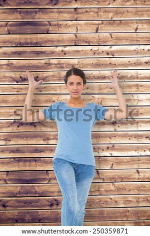 Annoyed brunette gesturing against wooden planks background - stock photo