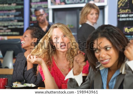 Annoyed business woman next to loud blond woman - stock photo