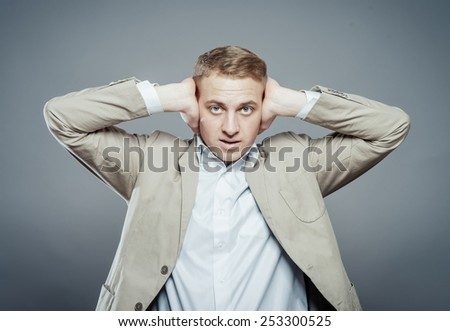 Annoyed businessman covering his ears with his hands, closing eyes.  - stock photo