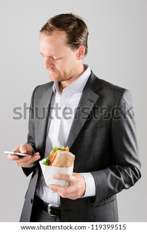 Annoyed businessman with take away lunch sandwich working on his phone texting a message - stock photo