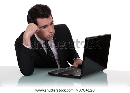 Annoyed businessman working on his laptop