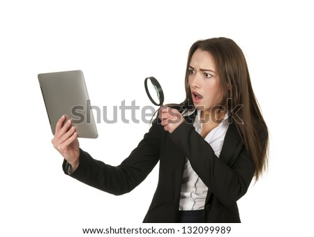 annoyed  businesswoman with tablet pc and magnifying glass - stock photo