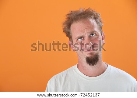 Annoyed Caucasian man looking up on an orange background