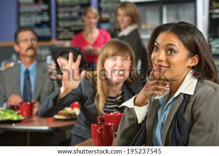 Annoyed coworker behind smiling business woman in cafeteria - stock photo