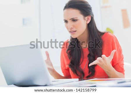 Annoyed designer gesturing in front of her laptop in her office