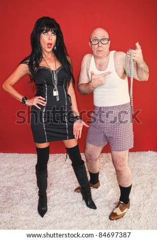 Annoyed dominatrix woman waits as her fearful client sees her tools. - stock photo