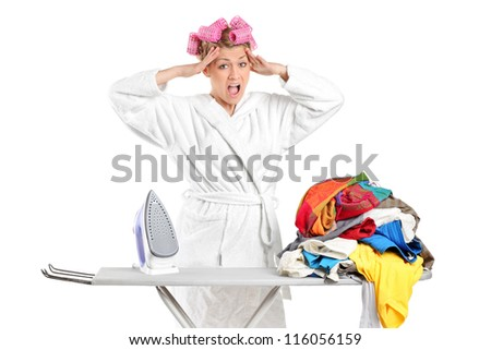 Annoyed housewife with ironing board and clothes isolated against white background - stock photo