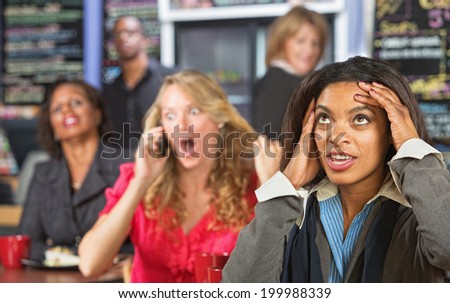 Annoyed lady listening to obnoxious woman on phone - stock photo