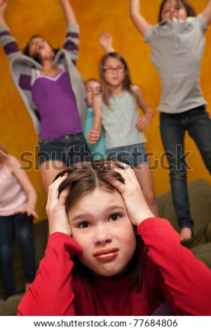 Annoyed little girl among others who shout and jump on furniture - stock photo