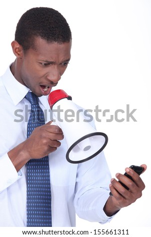 Annoyed man using a loudspeaker to shout at his cellphone - stock photo