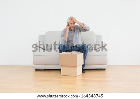 Annoyed mature man using cellpone while sitting on sofa with boxes in a new house