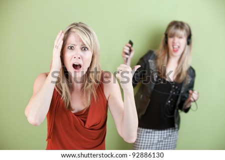 Annoyed mom with daughter listening on headphones - stock photo