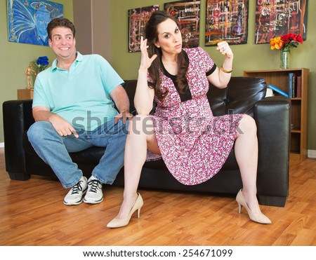 Annoyed pregnant woman threatening to punch grinning man - stock photo