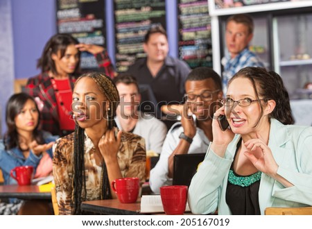 Annoyed students watching loud woman on cell phone - stock photo