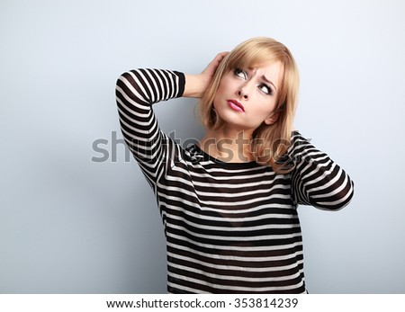Annoyed unhappy thinking young woman looking up on blue background - stock photo