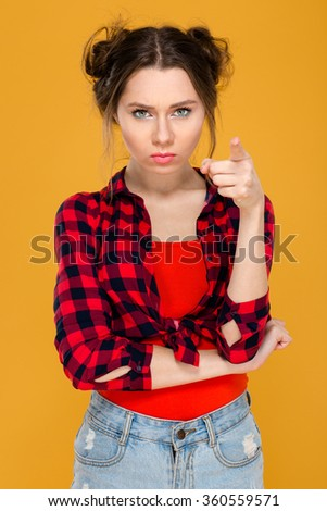 Annoyed unpleased young woman in checkered short standing and pointing on camera over yellow background - stock photo