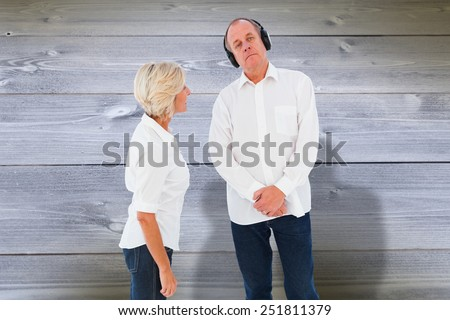 Annoyed woman being ignored by her partner against bleached wooden planks background - stock photo