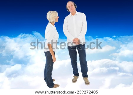 Annoyed woman being ignored by her partner against bright blue sky over clouds - stock photo