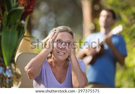 Annoyed woman covering ears with performer in background - stock photo