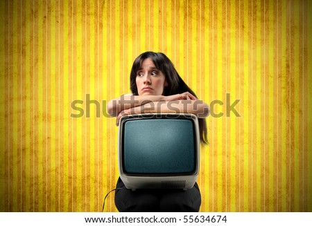 Annoyed woman holding an old television on her knees - stock photo