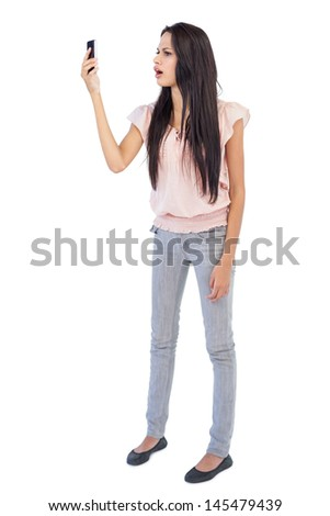 Annoyed woman looking at her cellphone on white background - stock photo