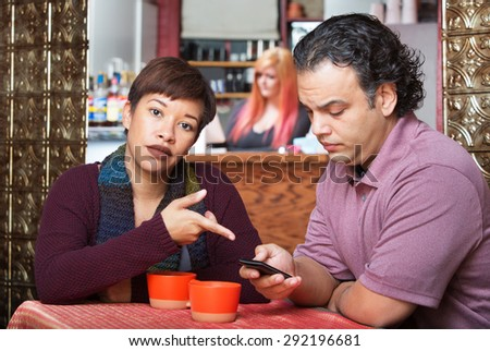 Annoyed woman pointing at cell phone held by man - stock photo