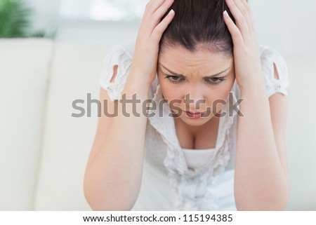 Annoyed woman sitting on the couch in the living room and holding her head in her hands - stock photo