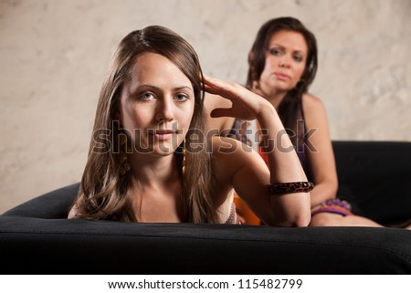 Annoyed woman turns her head away from lady on sofa - stock photo