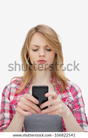 Annoyed woman using a mobile phone against a white background - stock photo