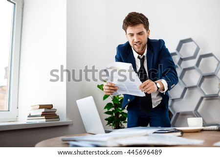 Annoyed young businessman  rummaging in papers, office background.