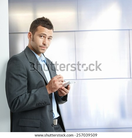 Annoyed young caucasian businessman in suit with tablet, standing in front of wall at business office. Looking at camera, copyspace. - stock photo