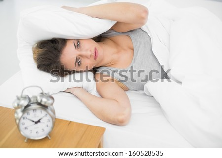 Annoyed young woman lying on her bed covering her ears with pillows at home - stock photo