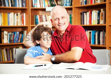 Annoying father teasing his son when they are supposed to be studying at the library.   - stock photo