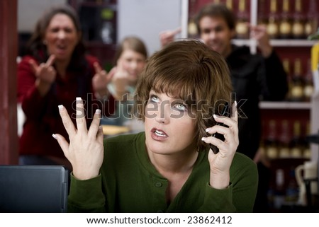 Annoying woman in a cafe on her cell phone gets the finger - stock photo
