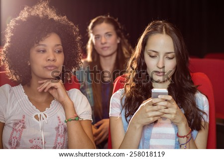 Annoying woman texting during movie at the cinema - stock photo