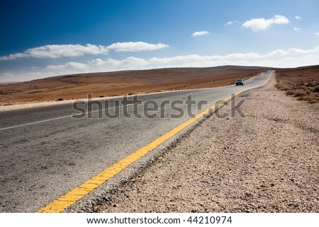Anonymous car driving toward the viewer on a desert road. - stock photo
