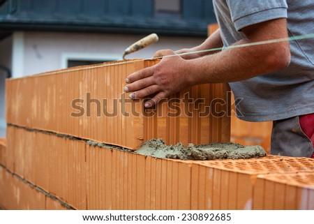 anonymous construction worker on a building site when building a house built a wall of bricks. brick wall of a solid house. icon image for undeclared work and bungling - stock photo