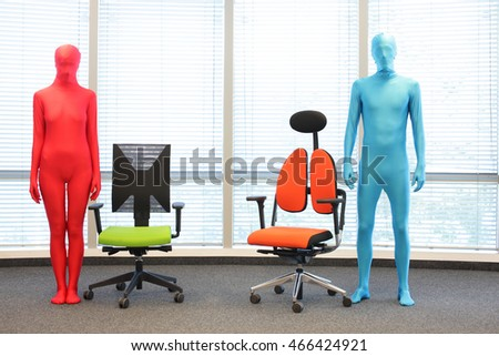 anonymous couple in full body elastic suits standing at  armchairs in office space