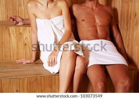Anonymous couple sitting next to each other in sauna - stock photo