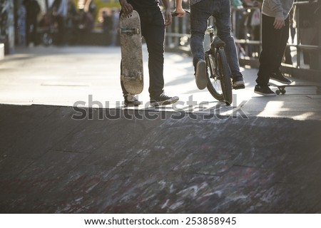 Anonymous friends at a skate park with a bike and skateboards - stock photo